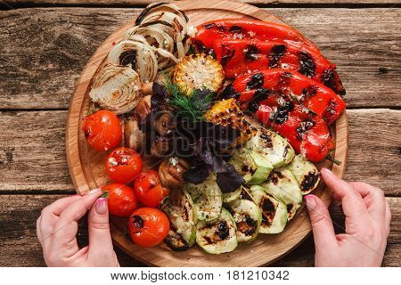 Chef laying out grilled vegetables on wood platter placed on wooden rustic table, top view. Food decorating. Kitchen, healthy eating, vegetarian cuisine concept