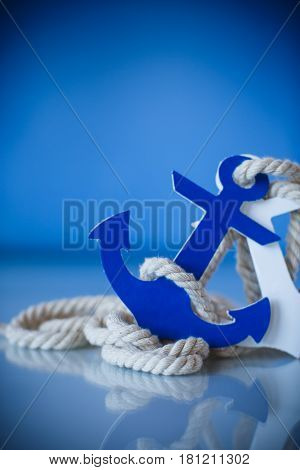 Wooden decorative anchor on the blue background