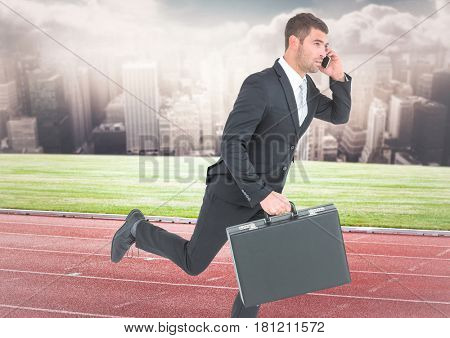 Digital composite of Business man on phone with briefcase and running on track against skyline with clouds