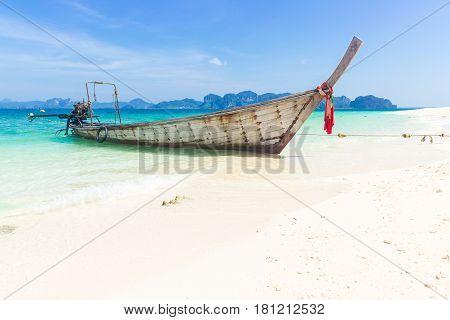 Thailand summer travel sea Thai old wood boat at sea beach Krabi Phi Phi Island Phuket park on white sand blue sky emerald green ocean water.