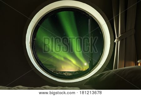 Interior circle window in bedroom with beautiful Northern lights (Aurora Borealis) view at night
