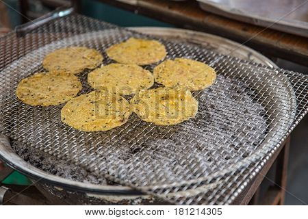 Thai traditional sesame dough sheet grill snack with old charcoal toaster.