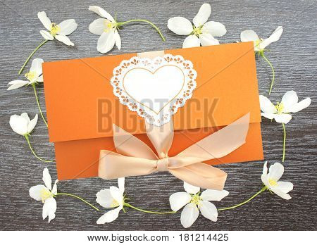 Beautiful greeting envelope on wooden background with flowers of Apple