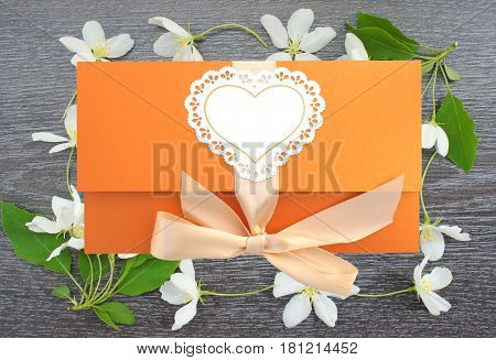 Beautiful orange greeting envelope on wooden background with flowers of Apple