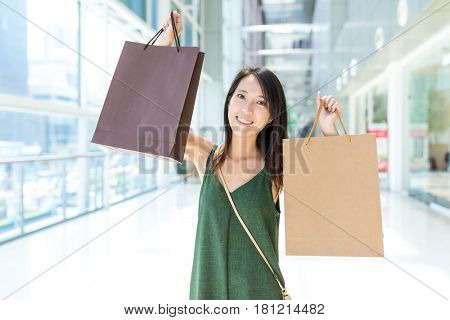 Thrilled woman holding up shopping bag in the mall