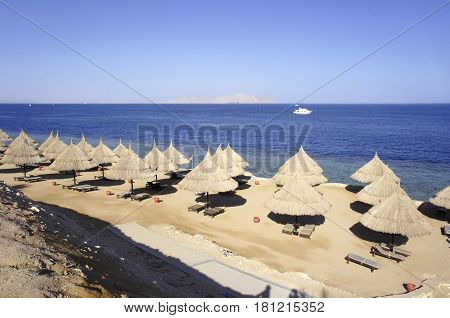 Beach with thatched umbrellas in Egypt and the sea with a sailing yacht