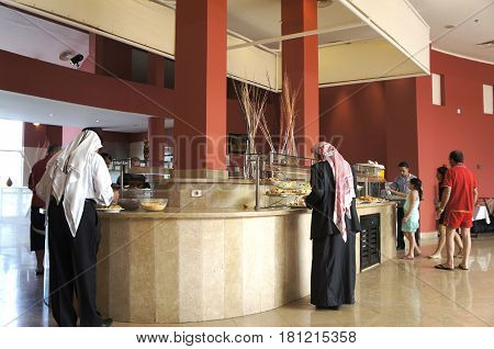 SHARM EL SHEIKH, EGYPT - MAY 20, 2016: Arab men in traditional clothing applied food in the buffet restaurant