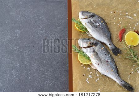 Fresh raw dorado fish on a piece of paper with lemon, rosemary, lemon, cherry tomato on a greay background. Healthy eating concept. Mediterranean life style.