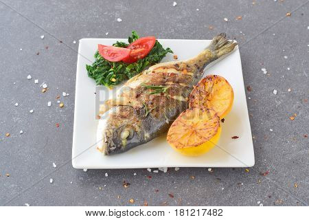 Fresh raw dorado fish on a piece of paper with lemon, rosemary, lemon, cherry tomato on a greay background. Healthy eating concept. Mediterranean life style
