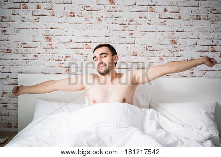 Cheerful Young Man Is Waking Up After Sleeping In The Morning Lying In The Bed