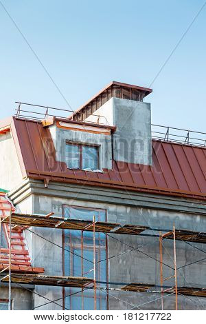 Building Site With House Under Construction. Scaffolding In Front Of Renovated House.