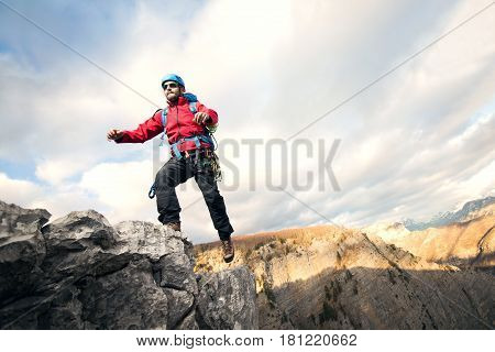 Mountaineer jumps over rocks in mountin cloudy weather