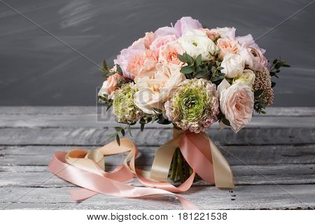 Bridal bouquet. Wedding. Beautiful bouquet of white, pink flowers and greenery, decorated with long silk ribbon. On a gray background.