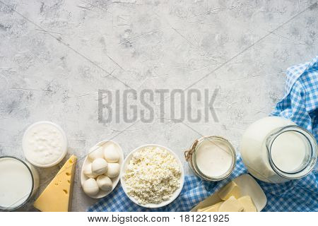 Selection of Dairy products. Cottage cheese or curd, yogurt, Sour cream, milk and mozzarella at concrete table. Top view copy space.