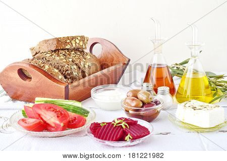 Greek food, mezedes. Jars with olive oil and vine vinegar, olives, feta, tzatziki, dark bread, raki, beetroot, fresh cucumber and tomato on a white background. Healthy eating concept. Healthy food