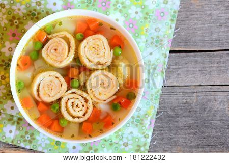 Vegetable soup with omelette rolls in a bowl on rustic wooden table. Diet soup with omelette, carrot, peas, leek, cauliflower and potatoes. Closeup. Top view