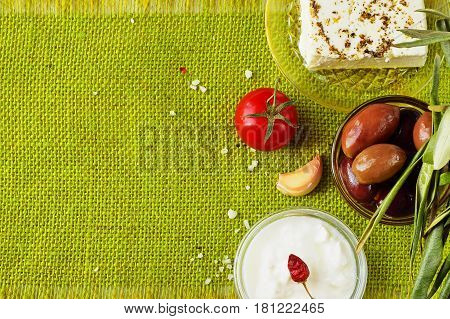 Green cloth background with the space for a text. Traditional Mediterranean motive - feta cheese, tzatziki, olives, garlic, jar with olive oil, tomato, beetroot, tomato, white dry wine. Healthy food
