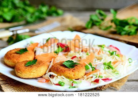 Chickpea cutlets and fresh vegetable salad on a plate. Fried chickpea cutlets. Cabbage salad with carrot, radish, green onions and parsley. Veggie lunch or dinner recipe. Rustic style. Closeup
