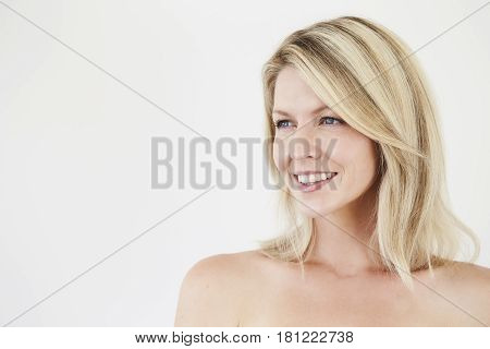 Gorgeous smiling blond woman in white studio