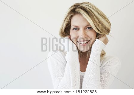 Gorgeous blond woman looking at camera studio