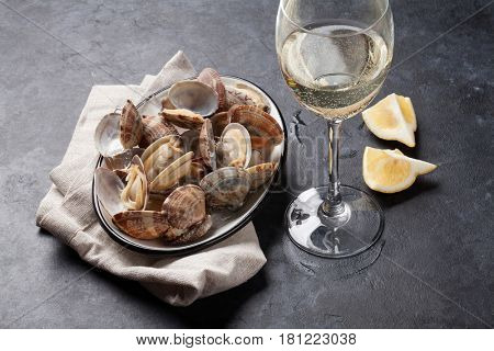 Fresh seafood bowl on stone table. Scallops and white wine