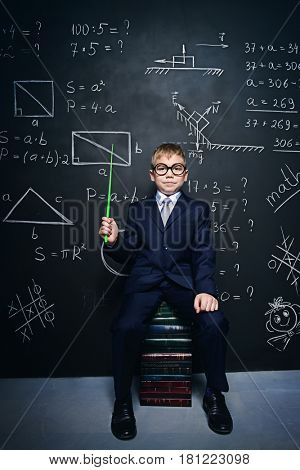 Smart schoolboy in black suit and glasses sitting on books over school blackboard. Educational concept.