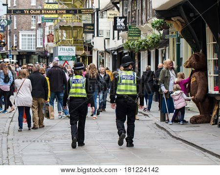 YORRK, UK - APRIL 7, 2017. Two British policemen on the beat and patrolling the city streets of York, UK amongst, shoppers and tourists.