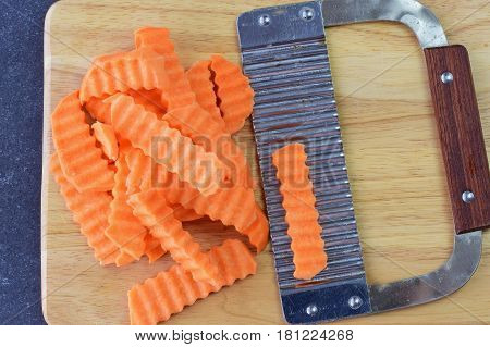 Yams, sweet potato cut in pieces with a special knife with ribs on a olive wood cutting board on a white background. Cooking step by step. Home cooking, Healthy eating concept