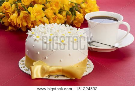 Cake with sugar paste flowers, on red background