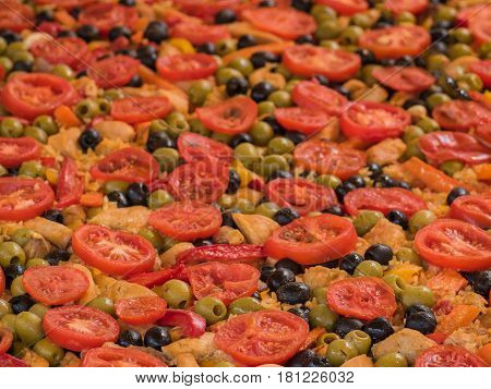 Paella with chicken meat tomato and olives