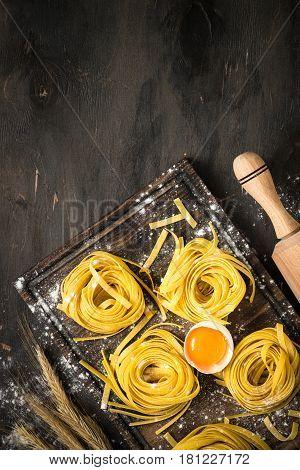 Fresh italian homemade pasta tagliatelle at wooden table. Italian food background.