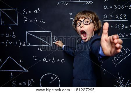 Smart schoolboy in black suit and glasses explaning something emotionally at the blackboard. Educational concept.