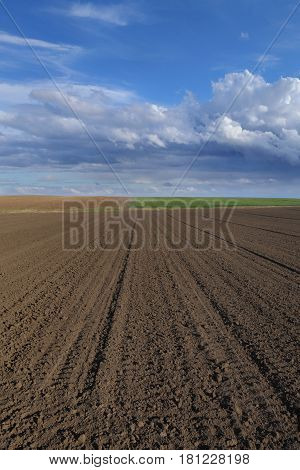 Cultivated field in early spring ground and sky with clouds