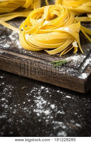 Fresh italian raw homemade pasta tagliatelle at wooden table. Close up with copy space.