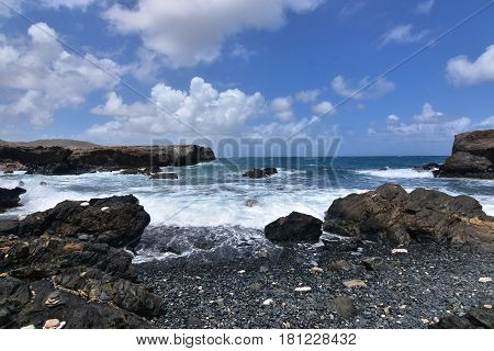 Waves gently rolling ashore on the black stone beach in Aruba.