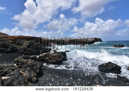Rugged lava rocks lining the shore of Aruba's black stone beach.
