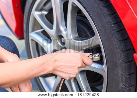 Woman Filling Air Into A Car Tire To Increase Pressure