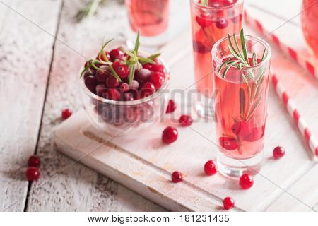 Refreshing drink with cranberries and rosemary on white wooden background selective focus copy space