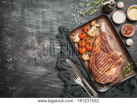 Succulent grilled tomahawk beef steak on the bone with seasonings fresh rosemary and grilled vegetables on a black background top view