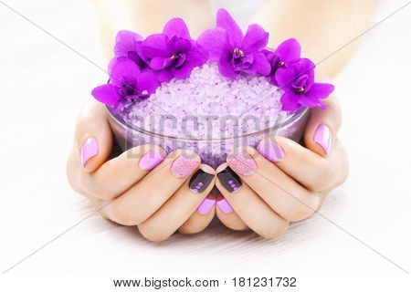 beautiful purple manicure with violet, candle and sea salt on the white wooden table. spa