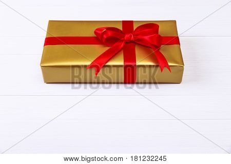 Gift box with red bow. Present wrapped with ribbon. Christmas or birthday golden paper package. On white wooden table.