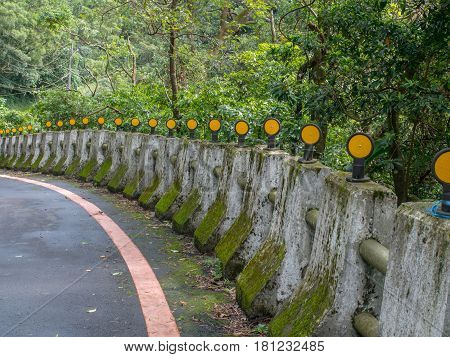 Concrete pillars / bumpers with yellow reflectors along asphalt road
