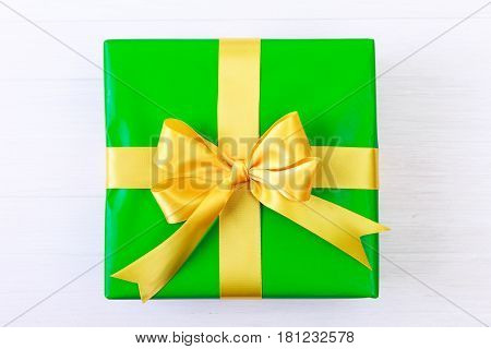 Gift box with yellow bow. Present wrapped with ribbon. Christmas or birthday green paper package. On white wooden table.