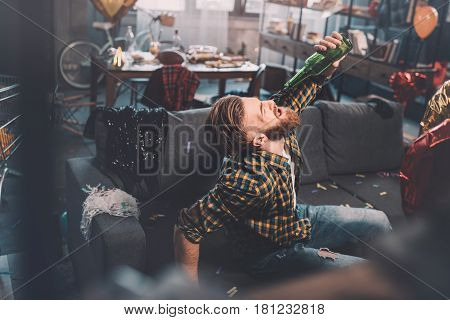 Bearded Young Man With Hangover Drinking Beer From Bottle In Messy Room After Party