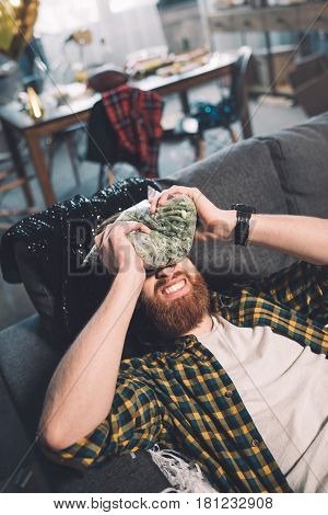Bearded Young Man With Headache And Hangover Lying On Sofa After Party