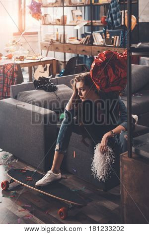 Young Upset Woman With Hangover Sitting On Couch In Messy Room After Party