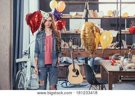 Upset Young Woman In Party Hat Standing In Messy Room After Party