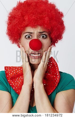 Anxious clown in red wig with bow tie
