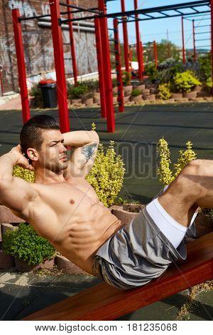 Man doing abdominal workout at outdoor gym, sunlit.