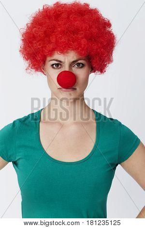 Annoyed clown in red wig portrait studio shot